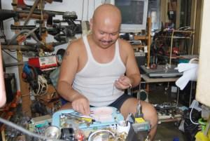 Junaedi sedang menyelesaikan perbaikan jam