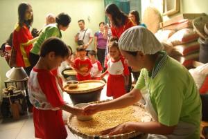 Murid KB/TK Yasa Luhur melihat proses menyortir kedelai sebagai bahan baku pembuatan makanan dan miniman di Rumah Wisata dan Wirausaha Kedelai di Argomas Timur.